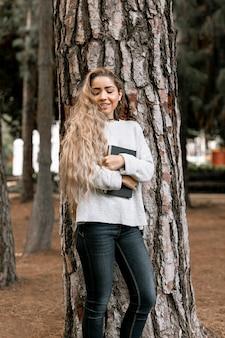 Donna di smiley in piedi accanto a un albero mentre si tiene un libro