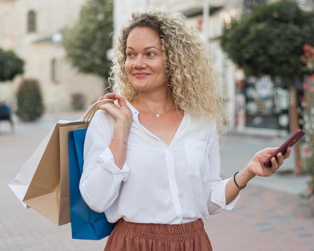 Donna di smiley vista frontale che tiene i sacchetti della spesa