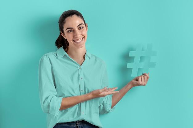 Donna di sorriso che tiene il segno di hashtag