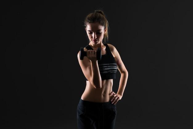 Donna di sport che fa sollevamento pesi su sfondo scuro