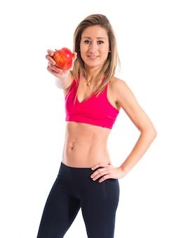 Donna di sport che tiene una mela