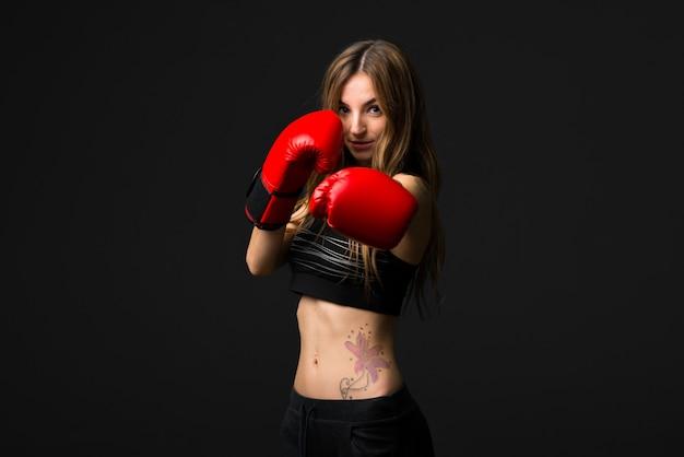 Donna di sport con i guantoni da boxe su sfondo scuro