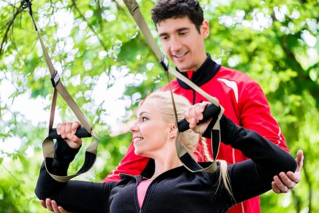 Donna di sport con l'istruttore all'allenamento della fionda