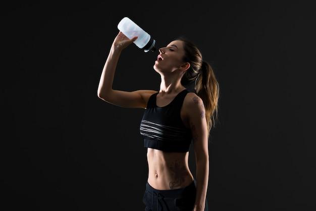 Donna di sport con una bottiglia di acqua su sfondo scuro