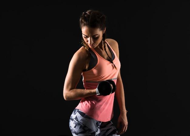 Donna di sport su fondo scuro che fa sollevamento pesi