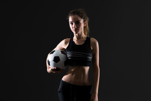 Donna di sport su fondo scuro che tiene un pallone da calcio