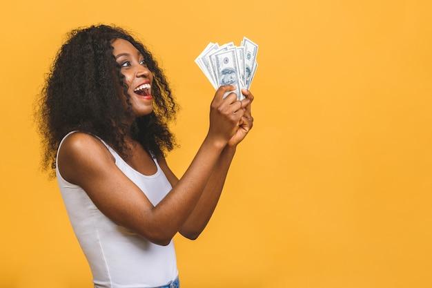 Donna di successo afroamericana che tiene un sacco di banconote in dollari di denaro