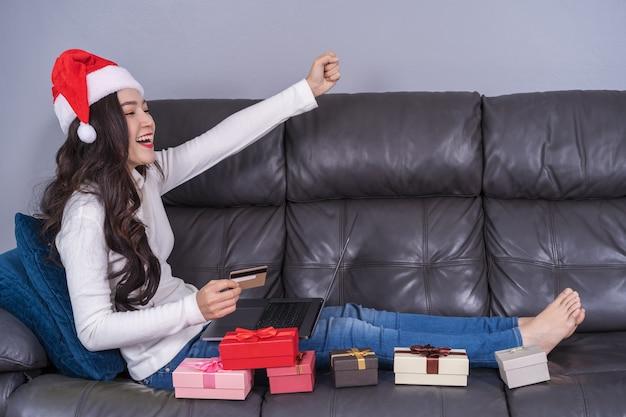Donna di successo nel cappello santa shopping online per il regalo di natale con il portatile in salotto