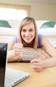Donna di successo shopping on-line sdraiato sul pavimento