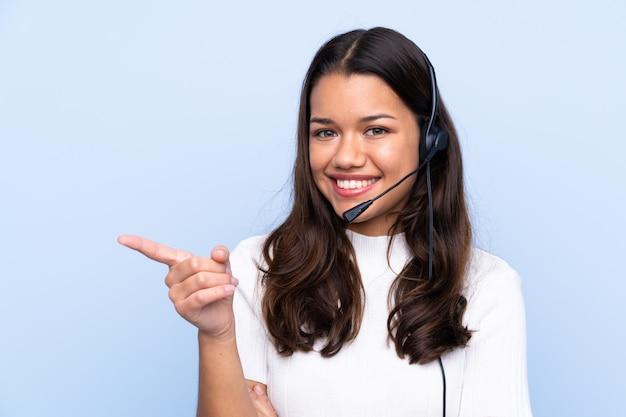 Donna di telemarketer che lavora con una cuffia avricolare sopra la parete isolata
