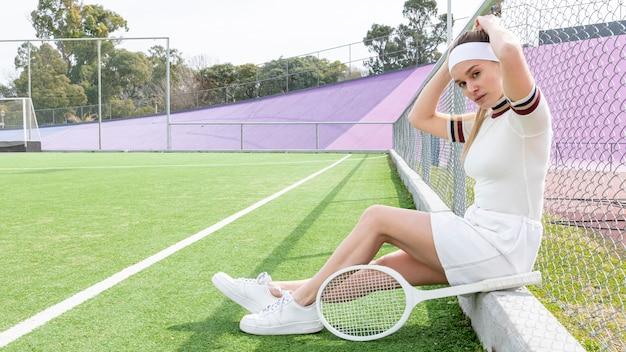 Donna di tennis che esamina macchina fotografica mentre sedendosi