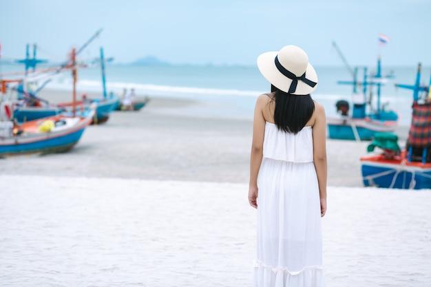 Donna di viaggio che cammina sulla spiaggia