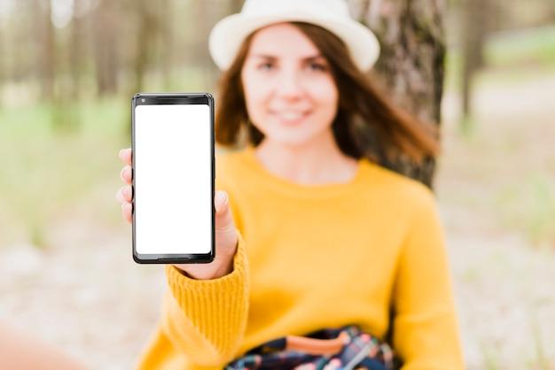 Donna di viaggio che mostra il suo schermo del telefono