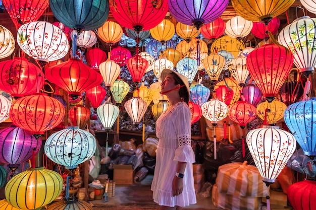 Donna di viaggio che sceglie le lanterne in hoi an, vietnam