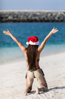 Donna di viaggio di vacanza della spiaggia di natale che porta il cappello e il bikini di santa che godono del natale sulla spiaggia tropicale. vista posteriore.