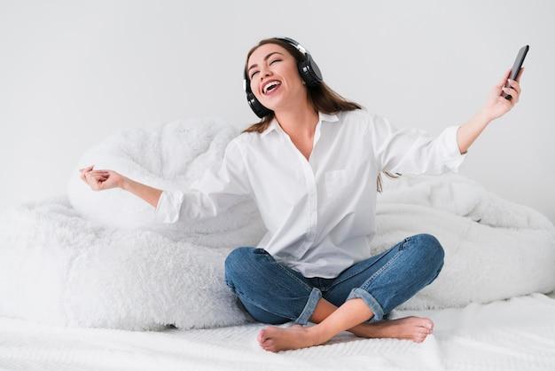 Donna di vista frontale che ascolta la musica e che canta