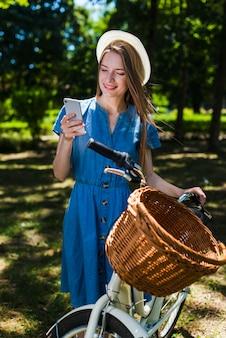 Donna di vista frontale che considera telefono