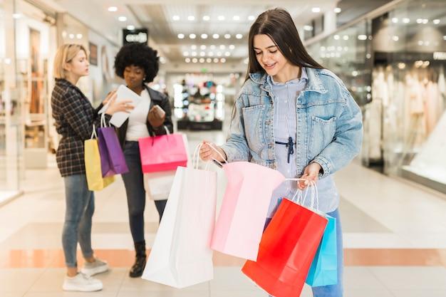 Donna di vista frontale che controlla i suoi sacchetti della spesa
