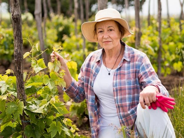 Donna di vista frontale che controlla il suo giardino