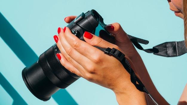 Donna di vista frontale che controlla le foto sulla macchina fotografica