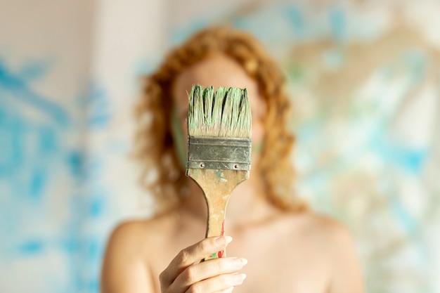 Donna di vista frontale che copre il viso con il pennello