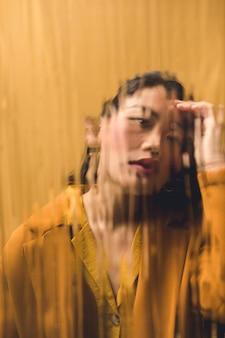 Donna di vista frontale che esamina la macchina fotografica dietro vetro bagnato