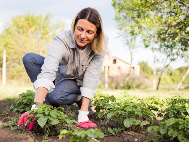 Donna di vista frontale che fa il giardinaggio all'aperto