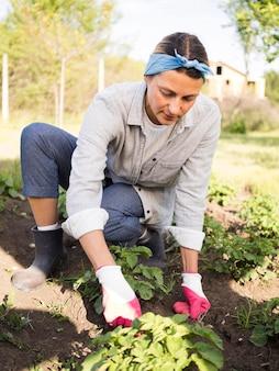 Donna di vista frontale che fa il giardinaggio fuori