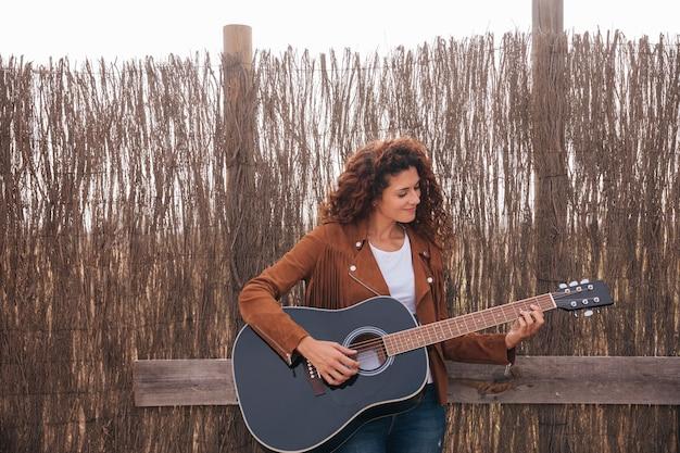 Donna di vista frontale che gioca chitarra