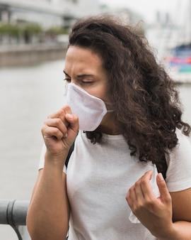 Donna di vista frontale che indossa maschera medica mentre tossendo