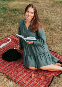 Donna di vista frontale che legge un libro su una coperta da picnic