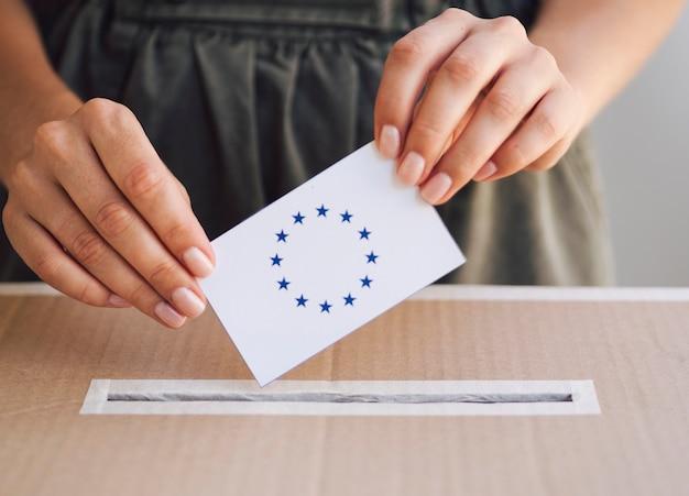 Donna di vista frontale che mette scheda elettorale in scatola