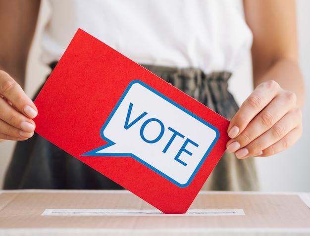 Donna di vista frontale che mette un messaggio di voto in una scatola