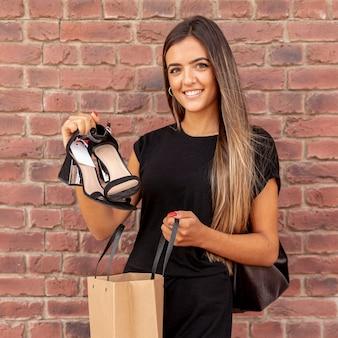 Donna di vista frontale che mostra le sue scarpe