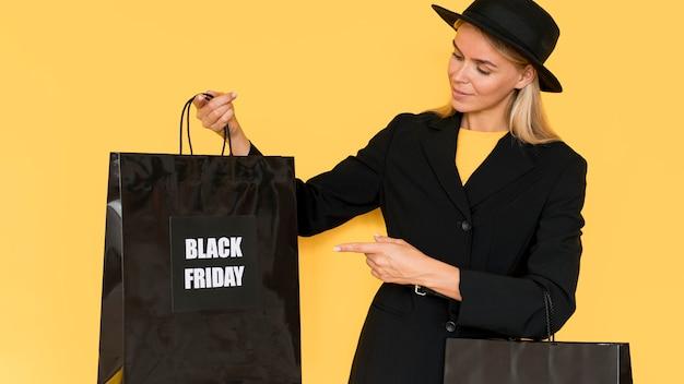 Donna di vista frontale che mostra una borsa della spesa venerdì nero