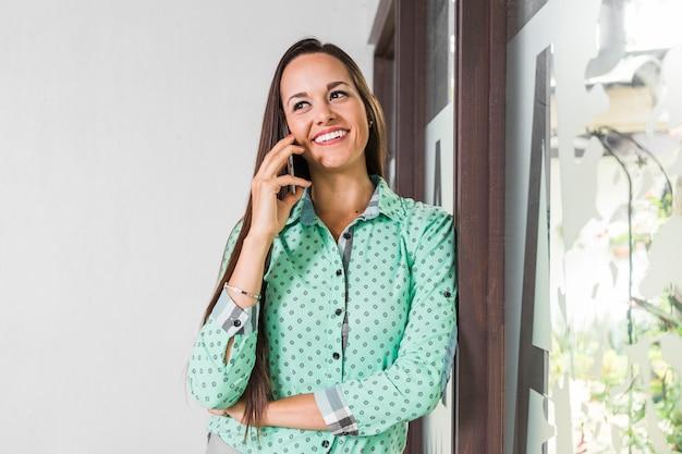 Donna di vista frontale che parla al telefono nel suo ufficio