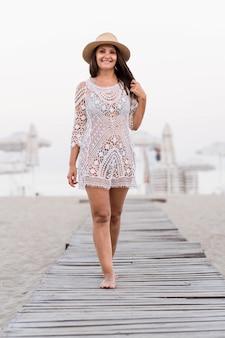 Donna di vista frontale che posa sulla spiaggia