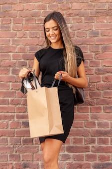 Donna di vista frontale che prende le sue scarpe dalla borsa