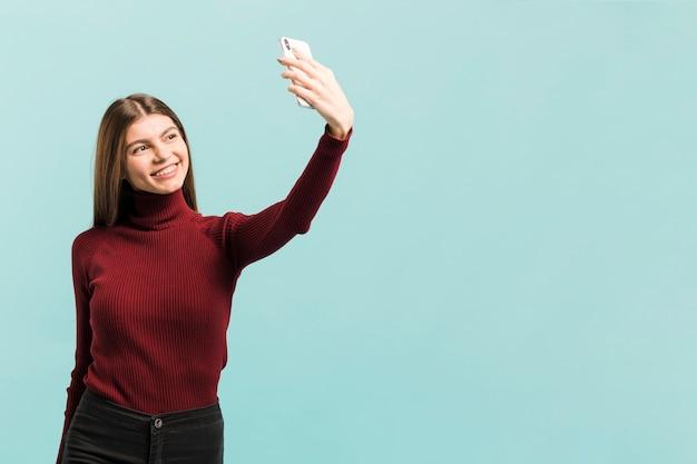 Donna di vista frontale che prende un selfie in studio