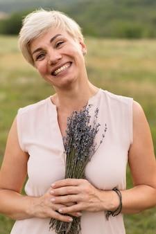Donna di vista frontale che propone con i fiori