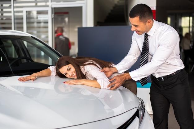 Donna di vista frontale che si appoggia automobile e maschio che la selezionano