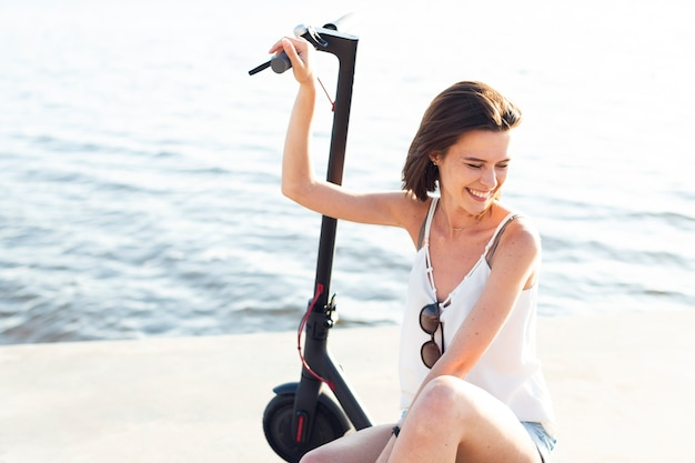 Donna di vista frontale che sorride e che posa su uno scooter