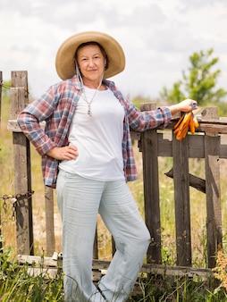 Donna di vista frontale che tiene alcune carote in sua mano mentre posando