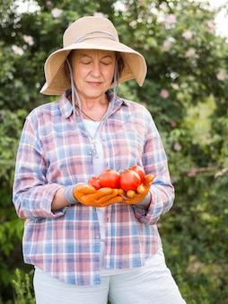 Donna di vista frontale che tiene alcuni pomodori freschi in sua mano