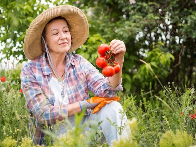 Donna di vista frontale che tiene alcuni pomodori in sua mano