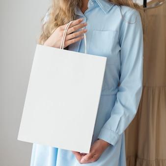 Donna di vista frontale che tiene il sacchetto della spesa