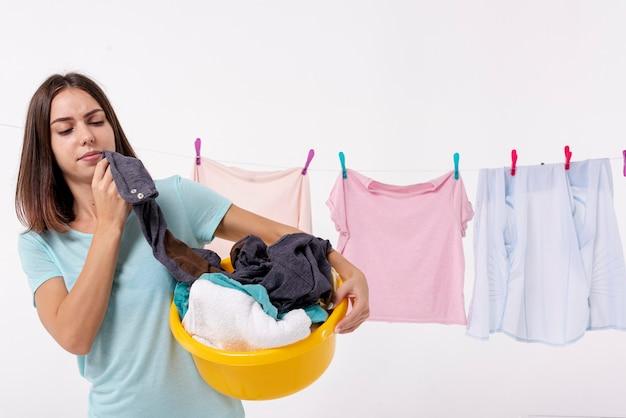 Donna di vista frontale che tiene un cestino di lavanderia giallo