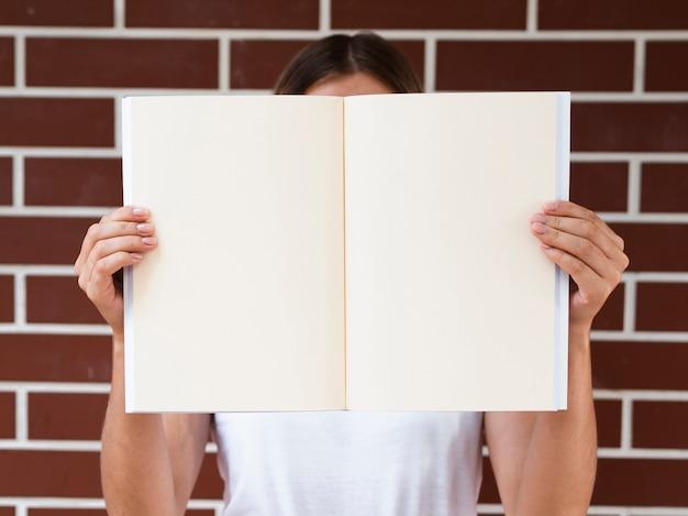 Donna di vista frontale che tiene una rivista del modello