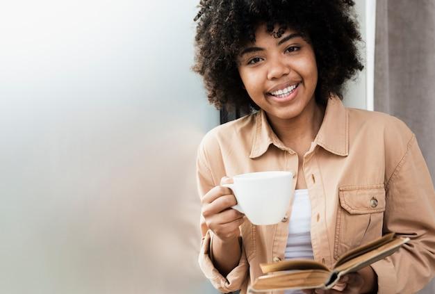 Donna di vista frontale che tiene una tazza di caffè e un libro
