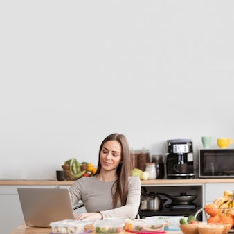 Donna di vista frontale con cibo e computer portatile